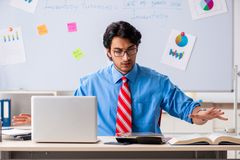 Young male financial manager working in the office. The young male financial manager working in the office stock photo