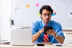 Young male financial manager working in the office. The young male financial manager working in the office stock photos