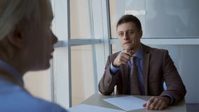 The young male finansial analytic has an interview in the consulting corporation. The confident worker wear suit with tie and blue shirt, holds a pen in his stock video footage