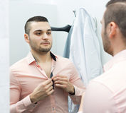 Young male at fitting-room. Portrait of young male with new clothes at fitting-room Stock Images