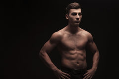 Young male flexing in dark studio background with hands on waist. Topless attractive young male flexing in dark studio background with hands on waist Royalty Free Stock Photography
