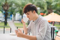 Young male freelancer using digital tablet in comfortable coffee Stock Photos