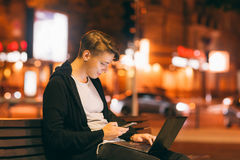 Young male freelancer working in city street. In night time, blurred lights background, free space. Smiling guy reading message on smartphone, while he working Stock Images