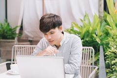 Young male freelancer working with laptop computer in comfortabl Stock Photo