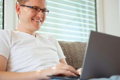 Young male freelancer working with laptop at home stock photos