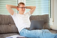 Young male freelancer working with laptop at home royalty free stock photography