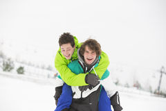 Young male friends enjoying piggyback ride in snow Royalty Free Stock Image