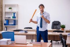 Young male furious employee holding baseball bat in the office