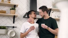 Young male gay couple hugging each other drinking morning coffee while standing at the kitchen at home. Gay. Relationships concept. Slow motion stock video