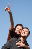 Young male giving his girlfriend piggyback ride. She pointing up with forefinger blue sky on background Stock Photos
