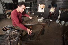 Young Industrial Artist. Young male glass worker with object and tools Royalty Free Stock Images