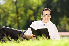 Young male with glasses lying on a grass with book Stock Images