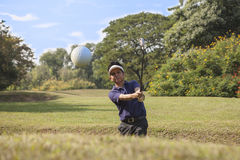 Young male golf player grey pants chipping golf ball out of a sa. Young male golf player in Blue shirt and grey pants chipping golf ball out of a sand trap with Royalty Free Stock Photo