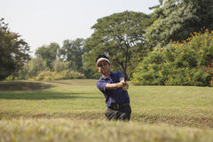 Young male golf player grey pants chipping golf ball out of a sa. Young male golf player in Blue shirt and grey pants chipping golf ball out of a sand trap with Stock Image