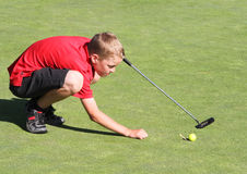 Young male golfer lining up putt. Young male golfer kneeling to line up putt Royalty Free Stock Photo