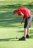Young male golfer putting. Preteen male golfer putting final shot Stock Photos