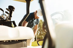 Young male golfer standing at the golf cart stock photo