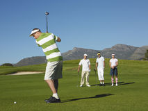 Young Male Golfer Teeing Off. Full length of young male golfer teeing off with competitors in background royalty free stock image