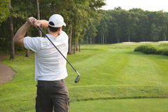Young male golfer tees off on a par three. Young male golfer in white shirt and white hat tees off with an iron on a par three Royalty Free Stock Photography