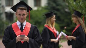 Young male graduate holding smartphone and smiling for camera, graduation event. Stock footage stock video footage