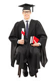 Young male graduate student sitting on chair and holding diploma Stock Image