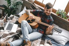 Young guitarist hipster at home with guitar in bedroom playing happy. Young male guitarist hipster indoors with guitar sitting on bed playing smiling royalty free stock photo