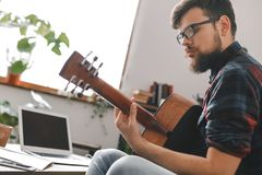 Young guitarist hipster at home holding guitar window light. Young male guitarist hipster indoors playing guitar close-up window light royalty free stock photos