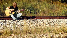 Young male guitarist playing sitting on the railway stock video