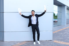Young male guy arab businessman laughing, rejoices success, hold Stock Image