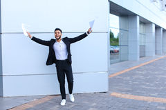 Young male guy arab businessman laughing, rejoices success, hold Stock Photos