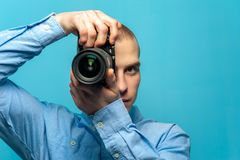 Young male guy photographer with dslr camera. Portrait of young male photographer examining his new camera while standing against a blue background. Place for royalty free stock image