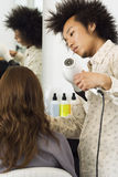 Young male hairdresser blow-drying woman's hair with hair dryer in salon, rear view Stock Images