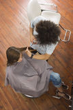 Young male hairdresser cutting woman's hair in salon, overhead view Royalty Free Stock Images