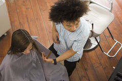 Young male hairdresser cutting woman's hair in salon, overhead view Stock Image