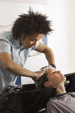 Young male hairdresser shampooing woman's hair in salon, side view Stock Photos