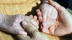 A young male hands comforting an elderly pair of hands of grandma outdoor close up. Stock Photos