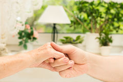 Young male hands holding old hands. On bright background Royalty Free Stock Photography