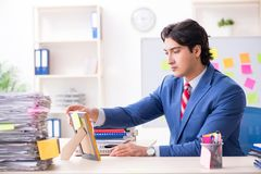 The young male handsome employee in conflicting priorities concept. Young male handsome employee in conflicting priorities concept royalty free stock photos