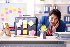 The young male handsome employee in conflicting priorities concept. Young male handsome employee in conflicting priorities concept stock photo