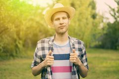 Young male happy smiling farmer in hat and casual shirt in countryside natural farm a stock photo