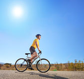 Young male with helmet riding a bike on a sunny day Royalty Free Stock Image