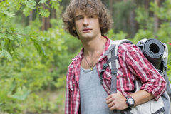 Young male hiker with backpack looking away in forest Stock Photos