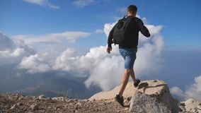 Young male hiker with backpack reaching up top of mountain with cloudy sky at background and raising hand. Man tourist