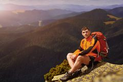Young male hiker with backpack relaxing on top of a mountain during calm summer sunset. Scenery from vacation - photo with space for your montage Stock Image
