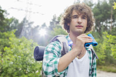 Young male hiker with binoculars in forest Royalty Free Stock Image
