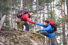 Young male hiker helping friend while trekking in forest Stock Photo