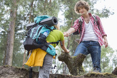 Young male hiker helping woman in climbing cliff at forest Stock Photo