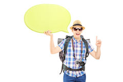 Young male hiker holding a speech bubble and gesturing with his. Young male hiker holding an empty speech bubble and gesturing with his finger isolated on white Royalty Free Stock Photo