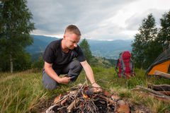 Young male hiker kindling firewood on the hill with tent Royalty Free Stock Image
