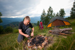 Young male hiker kindling firewood on the hill with tent Stock Image